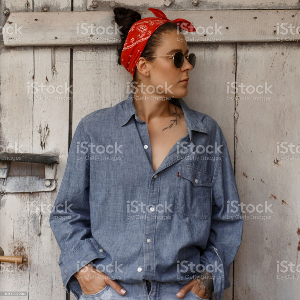 pretty hipster woman with sunglasses in fashionable denim clothes and blue fashion jeans stands near a vintage wooden wall stock photo download hipster kleidung
